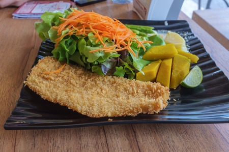 pescado frito: pescado fresco frito con patatas fritas servidos con ensalada verde Foto de archivo
