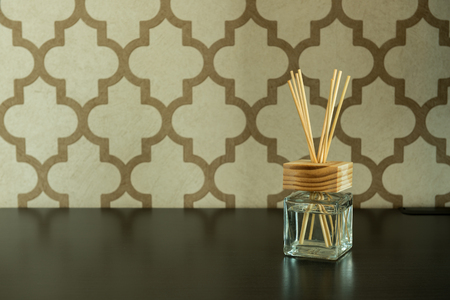 Aroma glass bottle and perfume stick on pattern wall background.Home accessories. Stock Photo