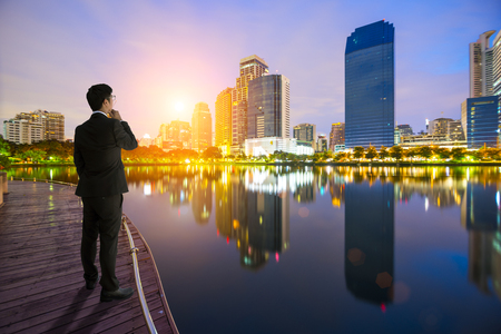 businessman looking at the city on sunrise. the concept of success, leadership and victory in business.