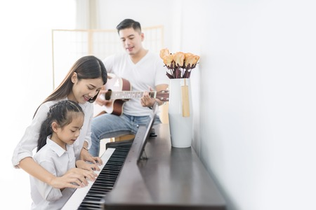 Asian family, mother  and daughter playing Piano,father playing guitar in family band at home, concept for family relationship Stockfoto