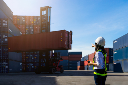 Woman Foreman control loading Containers box from Cargo freight ship for import export. Stock Photo