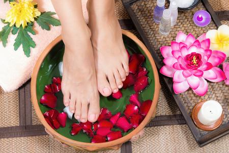 Closeup shot d'une femme pieds trempés dans l'eau avec des pétales dans un bol en bois. Belles pieds féminins au salon de spa sur la procédure de pédicure.