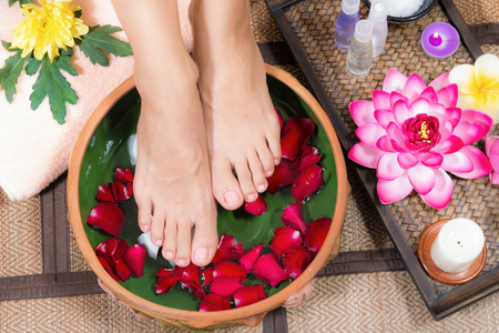 Closeup shot of a woman feet dipped in water with petals in a wooden bowl. Beautiful female feet at spa salon on pedicure procedure. 版權商用圖片 - 90867533