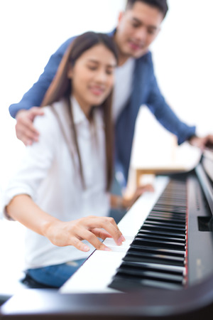 husband teaching his wife to play the piano, concept for family relationship Stock Photo