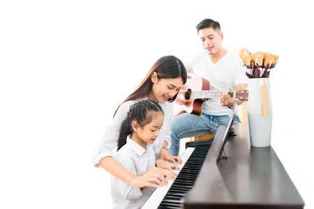 Asian family, mother  and daughter playing Piano,father playing guitar in family band at home, concept for family relationship 写真素材