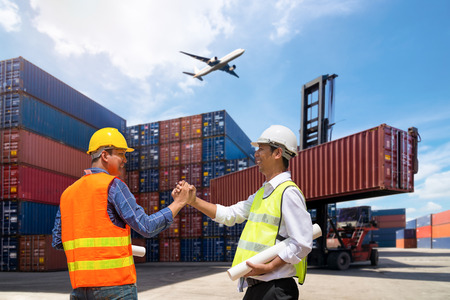 Foreman and Businessman control loading Containers box from Cargo freight ship Stock Photo
