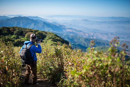 Professional photographer take landscape photos by camera on mountainon , travel , backpack