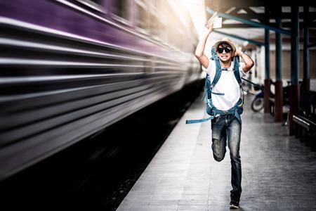 Hombre viajero corriendo tras un tren en movimiento desde una estación de tren Foto de archivo
