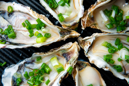 Close up open oysters on black plate.Healthy sea food.