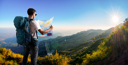 Traveler with map backpack relaxing outdoor with mountains on background 版權商用圖片