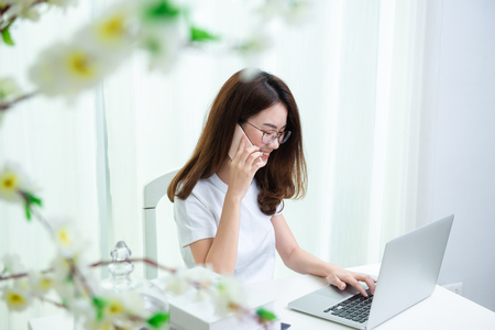 Young asian girl is freelancer with her private business at home office, Working with laptop and smartphone