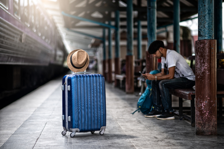 Traveler waits train at train station for travel in summer. Travel concept.