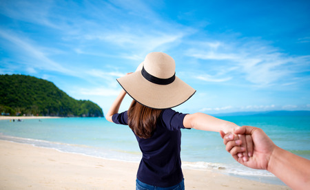 woman holding hand of her husband while running together on the beach , holiday vacation or valentine concept
