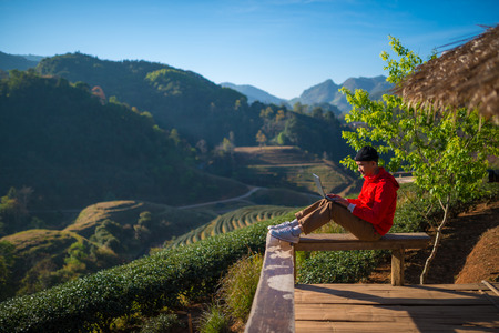 Traveller play laptop in morning with a view of the mountain landscape , network , communication
