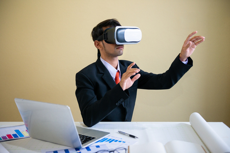 Business man working with laptop and using virtual reality glasses.analyzing data in office