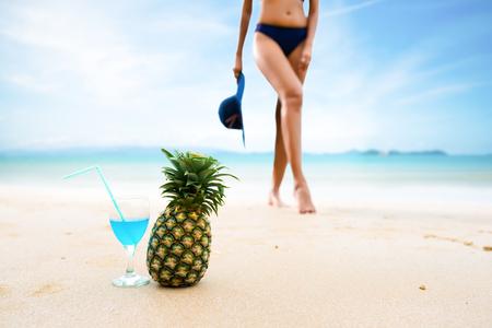 Sexy woman in the blue bikini and sunhat jumping on sea beach
