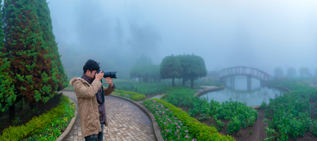 Landscape misty panorama , photographer taking pictures of foggy garden 스톡 콘텐츠