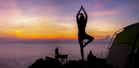Young woman practicing yoga in the nature.female happiness. Landscape background 스톡 콘텐츠