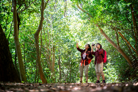 Two young Asian female hipster hiking in forest , wild , adventure. Travel concept