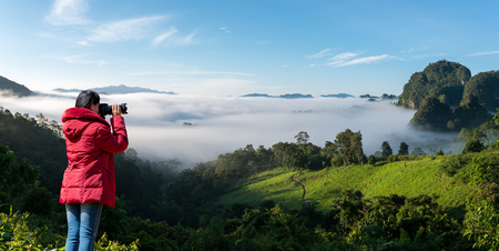 Nature photographer , Asian Woman Photographer are shooting the mist mountain in morning 스톡 콘텐츠