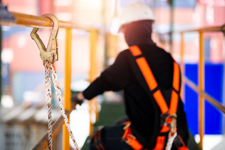 Construction worker wearing safety harness and safety line working at high place Zdjęcie Seryjne