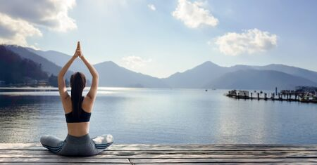 Young woman practicing yoga in the nature.female happiness. Landscape background Banque d'images