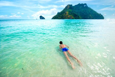 Young boy swim and relax in clear tropical sea. crystal blue sea of tropical beach.