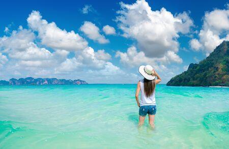 Happy traveller woman enjoys in tropical beach. summer vacation on a tropical beach