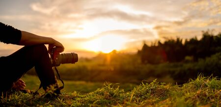 Nature photographer , Photographer are sitting look the sunset 스톡 콘텐츠