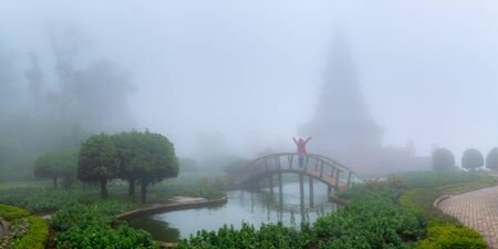 Traveller alone open arms and looking at foggy garden , travel , adventure , lifestyle