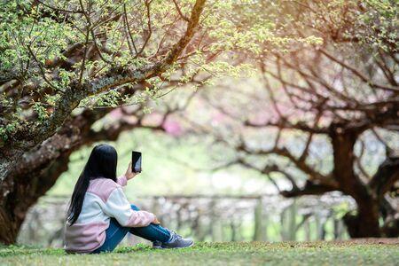 Asian woman traveler take selfie in the garden. travel winter 版權商用圖片
