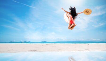 Sexy woman in bikini and sunhat jumping on sea beach