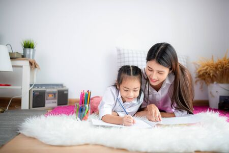 Asian happy loving family. pretty young mother write a book at home 스톡 콘텐츠