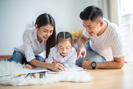Young family drawing together with colorful pencils at home, kids and happy people concept.
