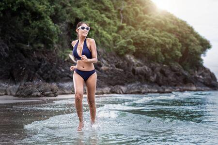 Sexy woman in the blue bikini and sunhat on sea beach.travel summer beach 版權商用圖片
