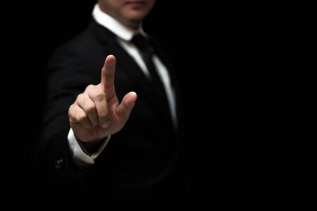 Businessman hand touching virtual screen , Hand pointing on empty space on black background 스톡 콘텐츠