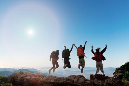Grupo de excursionistas felices saltando sobre la colina. vacaciones de senderismo, aventura salvaje