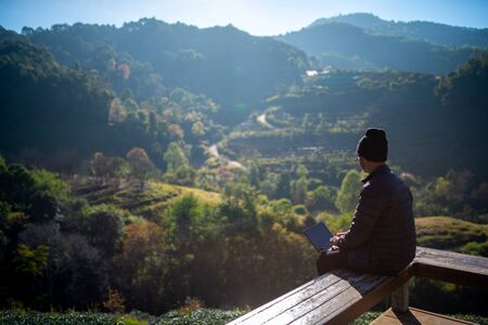 Traveller use laptop in morning with a view of the mountain landscape 스톡 콘텐츠