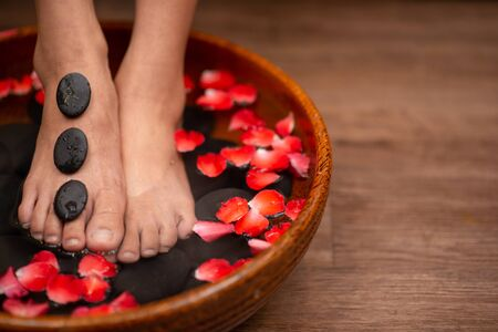 Closeup shot of a woman feet dipped in water with petals in a wooden bowl. Beautiful female feet at spa salon on pedicure procedure. 版權商用圖片 - 126573274