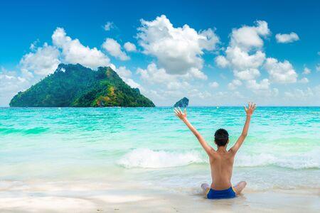 Glücklicher junger Reisender genießt den tropischen Strand. Sommerurlaub an einem tropischen Strand Standard-Bild
