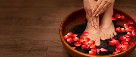 Closeup shot of a woman feet dipped in water with petals in a wooden bowl. Beautiful female feet at spa salon on pedicure procedure. 版權商用圖片 - 141263576
