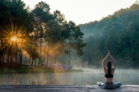 Young woman practicing yoga in the nature.female happiness. Landscape background Stockfoto