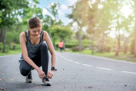 young asian woman runner doing tying shoelace. she athlete running at garden . sport , healthy 版權商用圖片 - 144723556