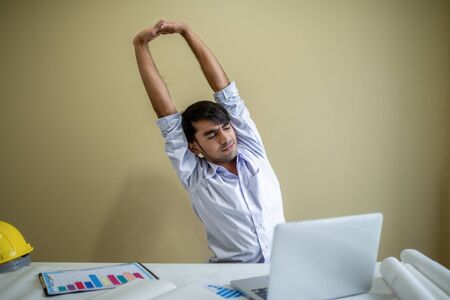 Business man working with laptop and documents on his desk.He stretching his Hands