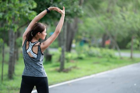 young asian woman runner doing stretch exercise stretching her arms. she athlete running at garden . sport , healthy