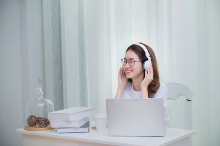 Happy Asian woman relaxing listen to the music connecting the internet with a laptop