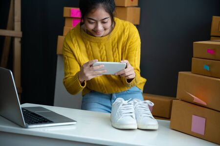 asian smiling girl using smartphone to shoot white sneaker posted for sale on the internet.startup small business owner working with tablet at workplace.happy owner & seller check product to customer 版權商用圖片 - 143671626