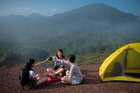 Group of Friends asian camp nature. Adventure Travel Relax Concept, mountain view.Group of Asian female tourists at the camp and drinking coffee in the mountains Stockfoto