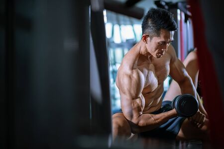 Asian man practice dumbbells in fitness gym . personal trainer 版權商用圖片 - 144723573