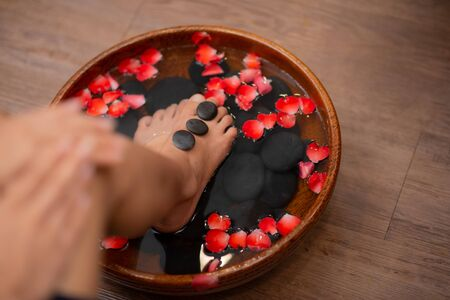 Top View shot of a woman feet dipped in water with petals in a wooden bowl. Beautiful female feet at spa salon on pedicure procedure.